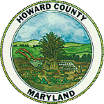 The seal of Howard County, Maryland depicting wheat, trees, rolling hills, and a blue sky background.